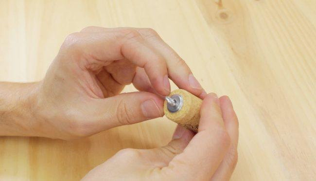Colocar el tornillo y las arandelas en el corcho