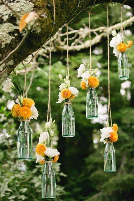 Botellas con flores para colgar de un árbol